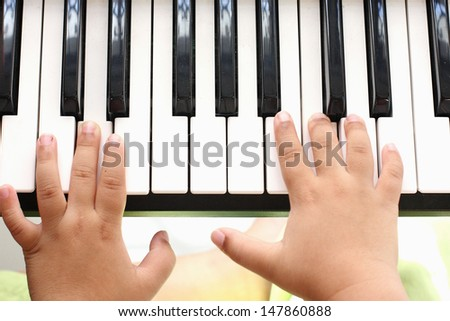 Hand of the boy. Playing the piano - stock photo