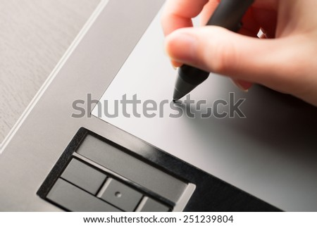 Hand of the designer with a pen on a tablet - stock photo