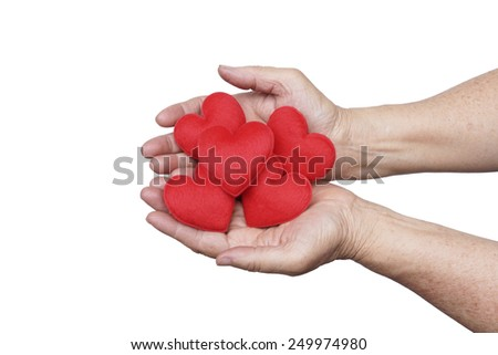 hand of the elderly female holding red hearts   - stock photo