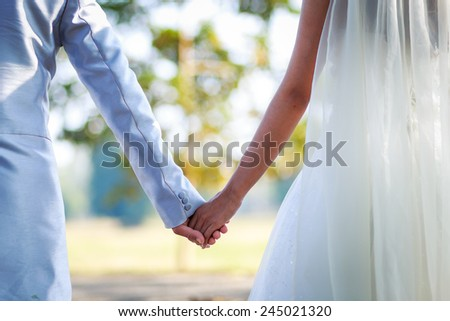 Hand of the groom and the bride. - stock photo