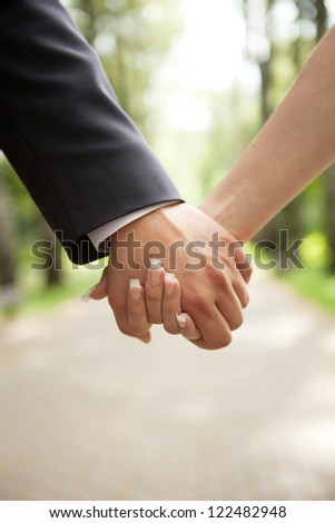 hand of the groom and the bride (guys and girls) on the back of the park - stock photo