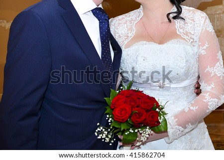Hand of the groom and the bride near wedding bouquet - stock photo