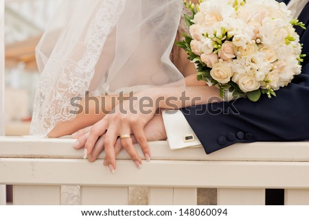 Hand of the groom and the bride with wedding bouquet - stock photo