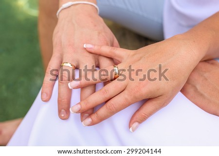 Hand of the groom and the bride with wedding rings. - stock photo