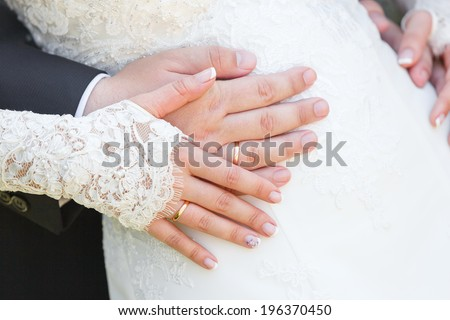 Hand of the groom and the bride with wedding rings at a wedding party - stock photo