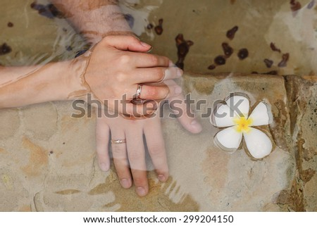 Hand of the groom and the bride with wedding rings in a swimming pool with plumeria flower. - stock photo