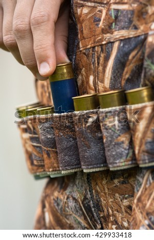 hand of the hunter pulling cartridge from the bandoleer - stock photo