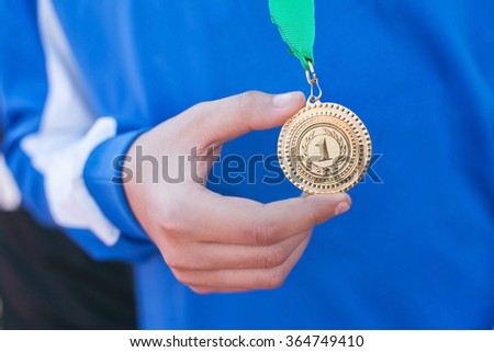 Hand of the man and medal close up. The winner holds a medal. Victory in competitions. First place. The hand holding a gold medal. Soccer winner.  - stock photo