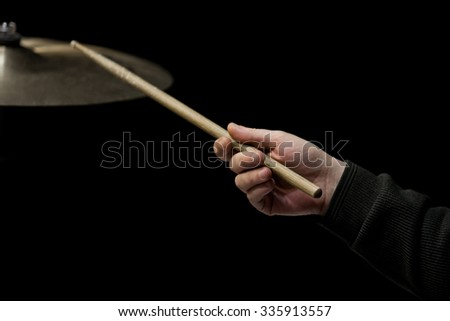 Hand of the musician with a drumstick on a black background