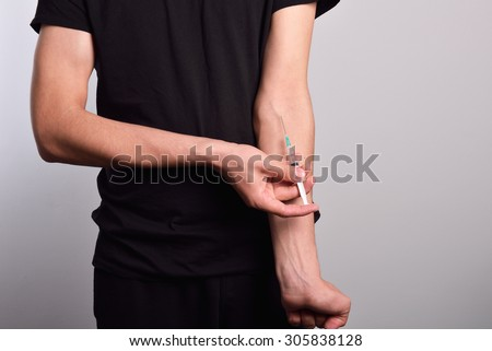 Hand of the narcotist preparing to inject drugs - stock photo