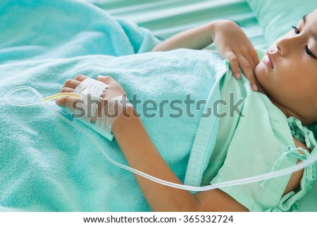 Hand of The Patient on the bed,little boy sick in the Hospital with saline intravenous (iv),focus hand