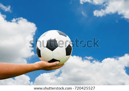 Hand of the teenager holding a soccer ball. the background is bright blue.