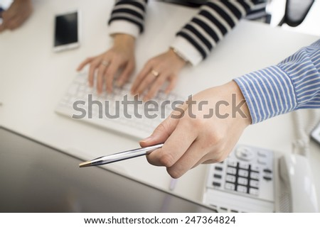 Hand of the woman pointing a monitor of computer - stock photo