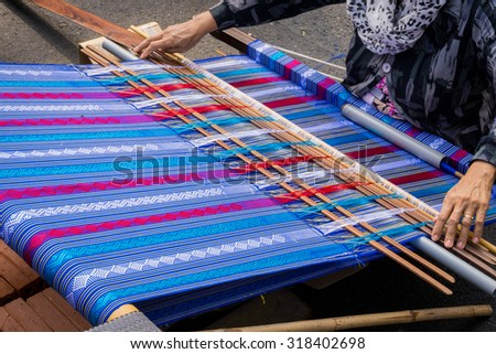 Hand of the woman weaves traditional fabric  - stock photo