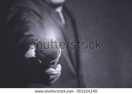 hand of vocalist holding microphone,back and white image