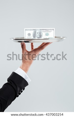 Hand of waiter in suit holding tray with money over white background