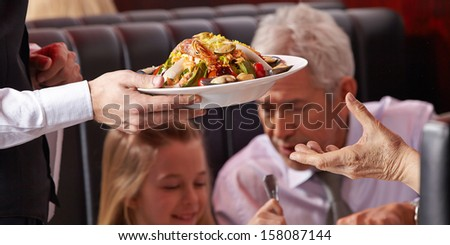 Hand of waiter serving seafood salad to elderly woman - stock photo