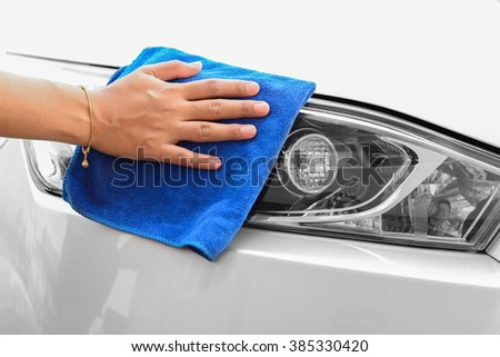 Hand of woman cleaning head lights of car with microfiber cloth - stock photo