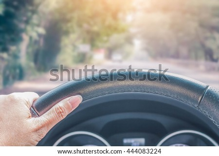 hand of woman driving car on the nature road