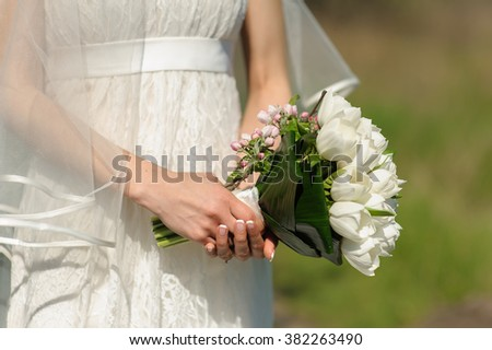 Hand of woman holds bouquet of white tulips and blooming sprig of apple on blurred green background in sunny spring day.
