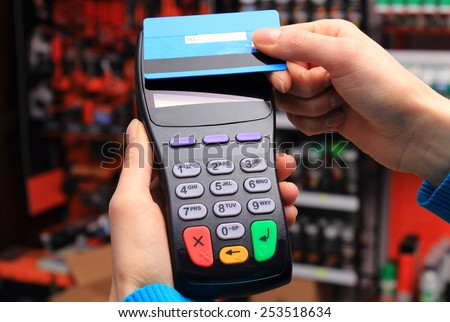 Hand of woman paying with contactless credit card with NFC technology in an electrical shop, credit card reader, payment terminal, finance concept - stock photo