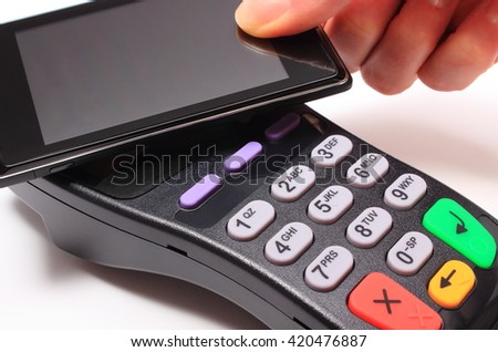 Hand of woman paying with NFC technology on mobile phone, credit card reader, payment terminal, finance concept