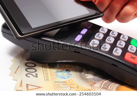 Hand of woman paying with NFC technology on mobile phone, credit card reader, payment terminal with cash, finance concept - stock photo