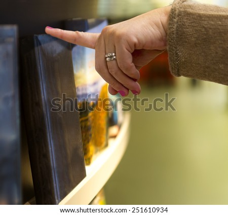 Hand of woman picking book from shelf  in bookstore - stock photo