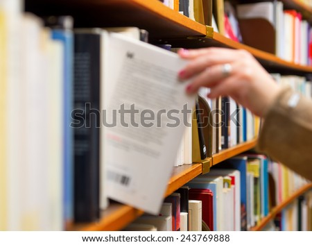 Hand of woman selecting a book from book shelf, blurred motion - stock photo