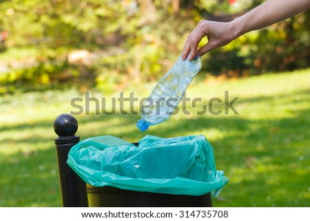 Hand of woman throwing plastic bottle into old trash can, concept of environmental protection, littering of environmental - stock photo