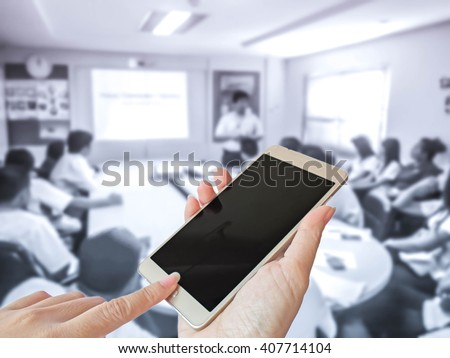 hand of woman turn off smart phone on blur photo of business people in the meeting room - stock photo