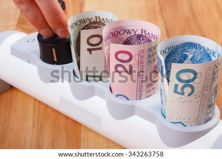 Hand of woman turns off plug from electrical extension, polish currency money, concept of saving money on electricity, energy costs - stock photo