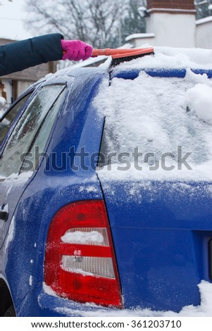 Hand of woman using brush and remove snow and ice from car and windscreen, concept of transportation and winter - stock photo