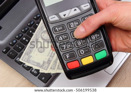 Hand of woman using payment terminal, enter personal identification number, credit card reader, currencies dollar on laptop, finance and banking concept