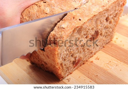 Hand of woman with knife slicing fresh baked wholemeal bread
