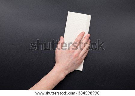 Hand of woman with white clean dry folded cleaning cloth - stock photo