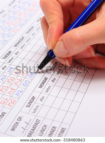 Hand of woman writing to medical form result of measurement sugar, concept of measuring sugar level