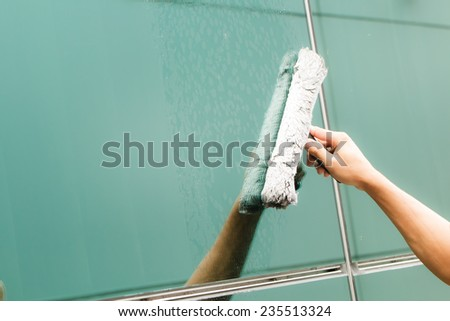 Hand of worker cleaning windows in building-1 - stock photo