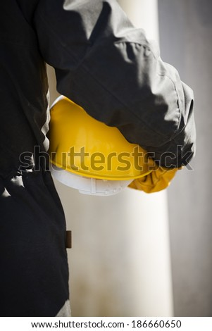 hand of worker with yellow hard-hat - stock photo