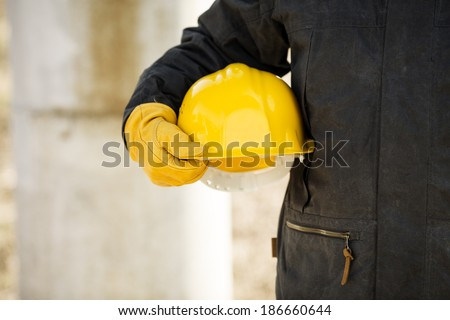hand of worker with yellow hard-hat, selective focus - stock photo