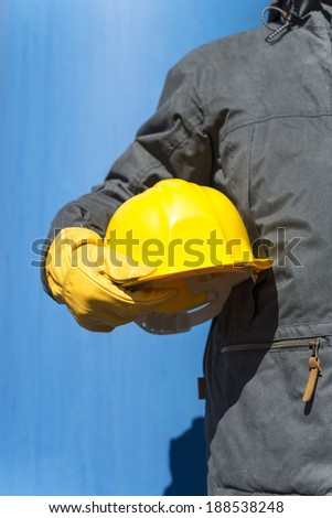 hand of worker with yellow hardhat - stock photo