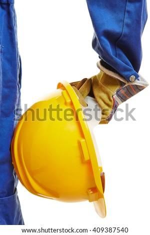 Hand of worker with yellow hardhat helmet - stock photo