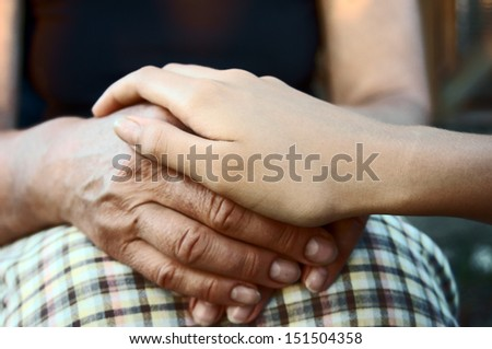 Hand of young girl comforting elderly hands in support close up                                - stock photo