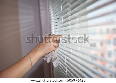 Hand of young woman cleaning blinds by cloth; housework (vignette)