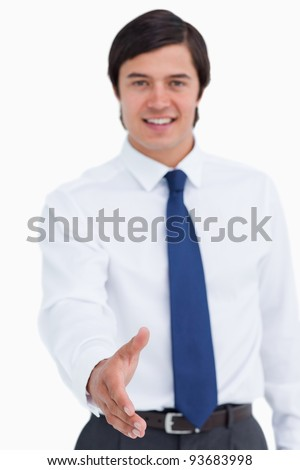 Hand offered by smiling young tradesman against a white background - stock photo
