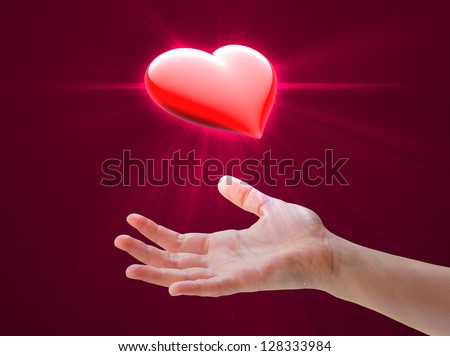 Hand offering or receiving shining love heart symbol - stock photo