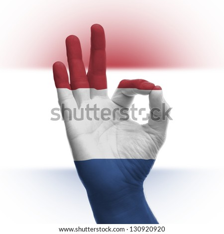 Hand OK sign, wrapped in the flag of the Netherlands - stock photo