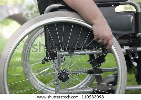 hand on a a wheel of wheelchair - stock photo