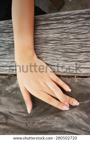 Hand on a background of brown wood