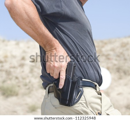 Hand on a handgun about to be pulled from the holster - stock photo